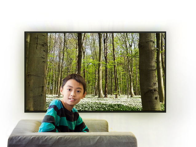 A boy sitting in front of a TV